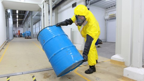 Worker in protective suit with barrel