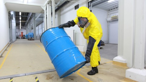 Worker in a protective suit handling a barrel.