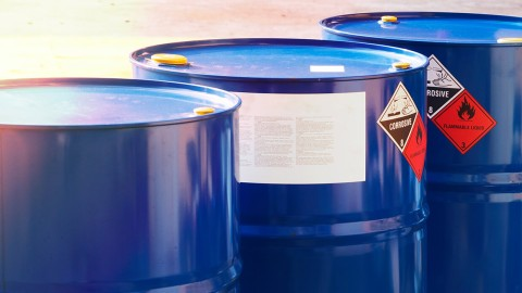 Close-up of chemical barrels with warning of corrosive substances